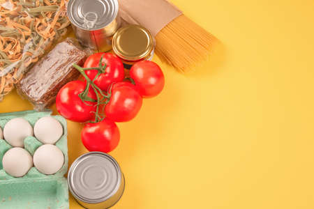 Food donations on yellow background with copy space - pasta, vegatables, canned food, cooking oil. Food bank and food delivering concept. Flat lay composition, selective focus