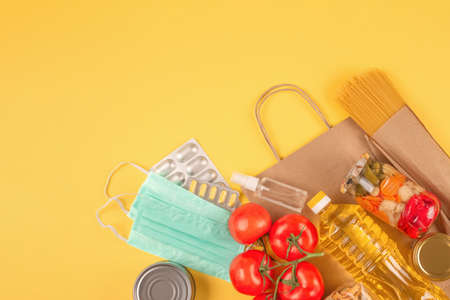 Food and medicines donations on yellow background with copy space - pasta, vegatables, canned food, cooking oil, hand sanitizer and face masks. Food bank concept. Selective focus, flat lay Standard-Bild