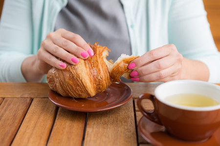 Woman with pink manicure is tearing a small piece from large croissant