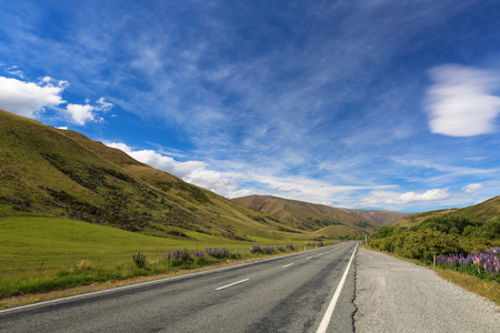 A straight country road between green hills in New Zealand. Bright blue sky with white clouds, sunny day