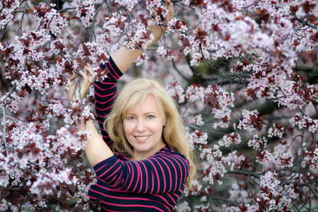 Happy smiling Caucasian blond woman with long hair in purple fedora hat near blossoming plum cherry tree Foto de archivo