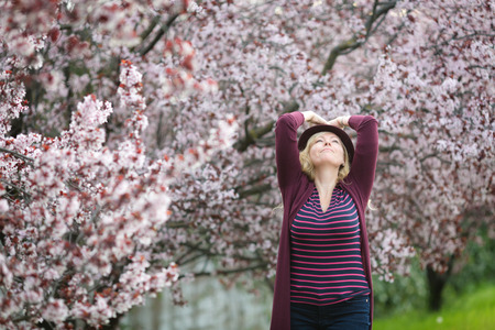 Caucasian blond woman with long hair in purple fedora hat near blossoming tree, looking in the sky, happy