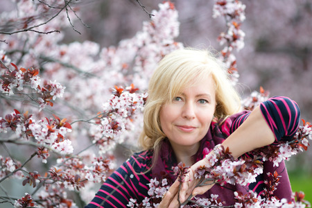 Portrait of happy smiling Caucasian blond woman with long hair near blossoming plum cherry tree, no teeth, looking to the camera