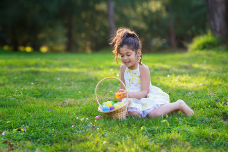 Little girl is sitting on green grass near basket with Easter eggs, looking to the basket off the camera