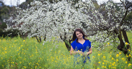 Waist up portrait of young woman in bright blue top in blossoming orchard and yellow mustard field, smiling, looking straight to the camera Foto de archivo