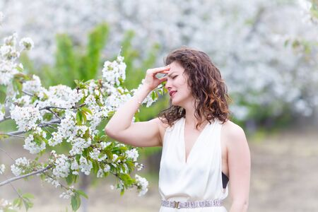 A portrait of Caucasian brunette woman near blossoming cherry tree. Painful emotions, headache