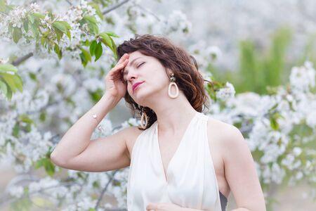 A portrait of Caucasian brunette woman near blossoming cherry tree. Painful emotions, headache