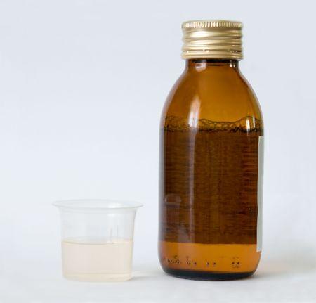 dosage: Bottle with liquid medicine and beaker for dosage