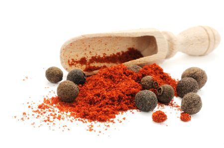 Wooden scoop in heap of pepper with peppercorns of sweet papper photo