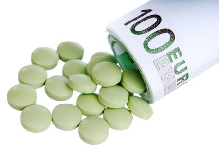 Green round pills fall out a sheaf of 100 euro papers photo