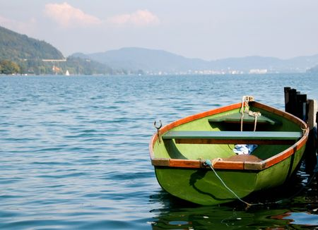 Green wooden boat on water with mountains on background
