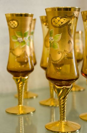 workmanship: Transparent gold tall hand-made glass covered with gold drawing. Shallow depth-of-field Stock Photo