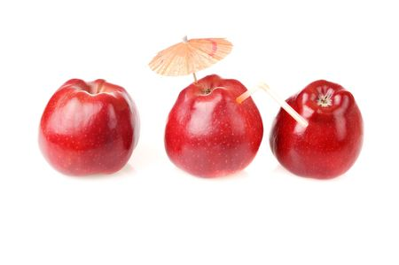 Two fresh red apples and one apple with cocktail tube and umbrella photo