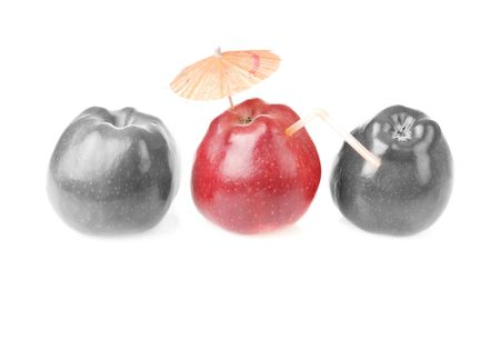 Two colourless red apples and one apple with cocktail tube and umbrella photo
