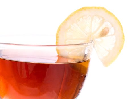 Brim of transparent cup with black tea and segment of a lemon on white background. Focus on right side of the cup. photo