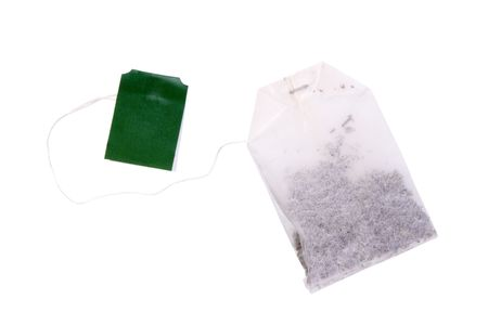 One teabag with black tea and green label isolated on white background photo