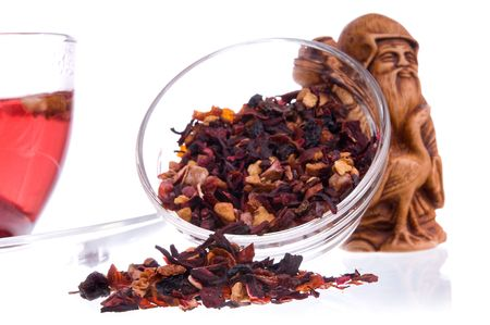 Healthy dry fruit tea in a transparent saucers and idol of prosperity statuette on background out of focus. Shallow depth-of-field, focus on tea heap. photo