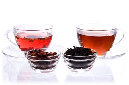Two transparent cups and saucers with liquid and dry black and fruit tea  photo