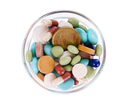 Fifty euro cents in glass saucer full of different pills on white background photo