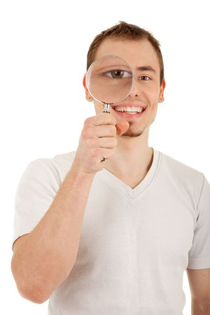 Young man in casual dress looks through magnifying glass. Focus on the mans face. Isolated on white background  photo