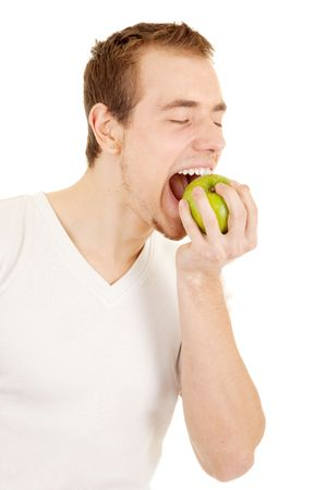 Young handsome man is biting a green apple on his palm. On white background. photo