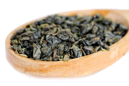Natural green tea leaves in wooden spoon. Shallow depth of field. photo