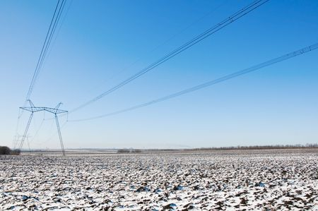 Line of electric pylons and long caples on winter snow-covered field Stock Photo - 6658762