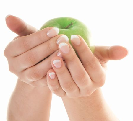 Green fresh apple in beutiful female hands with nice french manicure isolated on white background