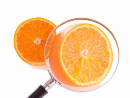 Juicy orange slice through magnifying glass. Shallow depth of fields, focus on orance in loupe.