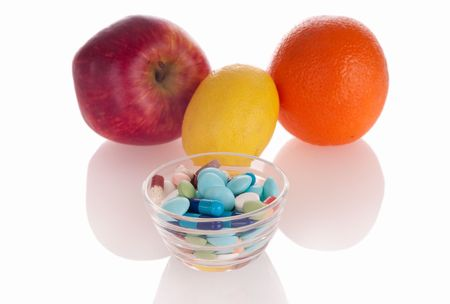 Concept of vitamin medicine with different pills in glass bowl and defocused fruits on background with soft shadows photo
