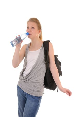 Nice girl in casual style is drinking clear water from plastic bottle isolated on white background photo