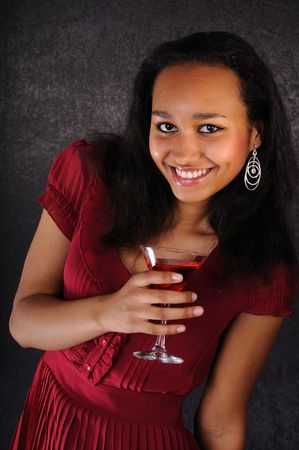 Attractive smiling young woman with red cocktail on black background photo