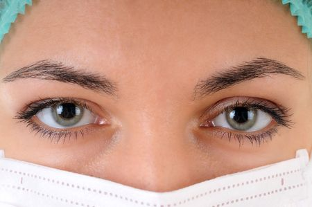 Close-up of a woman doctor's eye wearing a mask examining you.  Stock Photo - 7256176