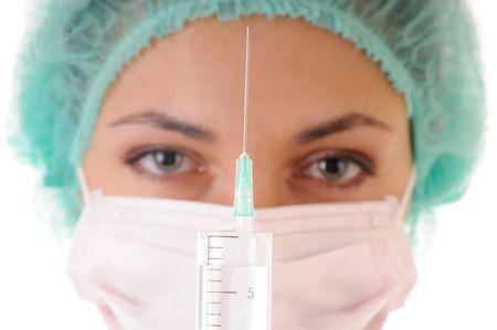 krankenschwester spritze: Spritze mit der L�sung f�r die Injektion und Frau in der Maske und cap auf Hintergrund. Konzentrieren sich auf die Spritze. Lizenzfreie Bilder