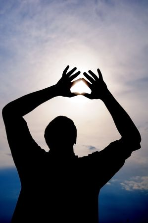 Male is holding the sun in his hands with heart symbol photo