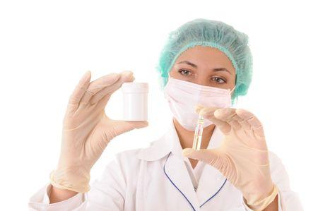 enfermera con cofia: Mujer en ropa de trabajo m�dico con botella y ampolla con medicamentos en las manos. Aislados sobre fondo blanco. Se centran en las manos.