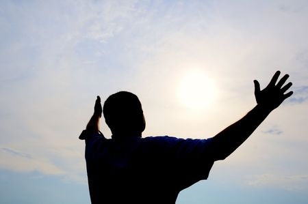 hands raised: Praying man. Silhouette.  Stock Photo