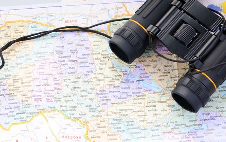 Concept of travel with binoculars on a map of Ukraine. photo
