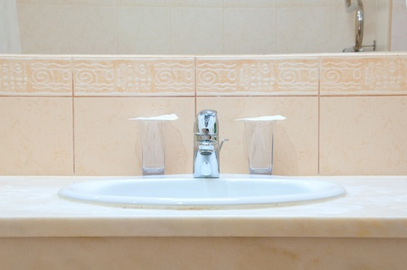 White sink, chrome tap and two glasses in a hotel bathroom Stock Photo - 8557950