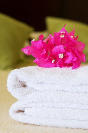 White towels with flowers on a bed in a hotel room. Selective focus on flowers.  photo