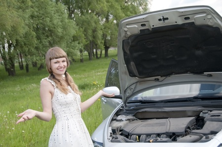 Worried young woman near her broken car with non-urban background photo