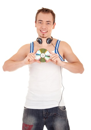 20 25: Young man in headphones holds a music CD isolated on white background Stock Photo