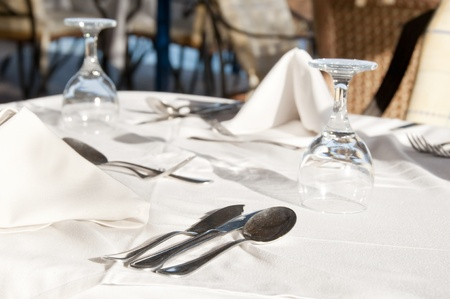 Dining tables ready for customers, outdoor evening. Shallow depth of fields, focus on the spoon top. photo