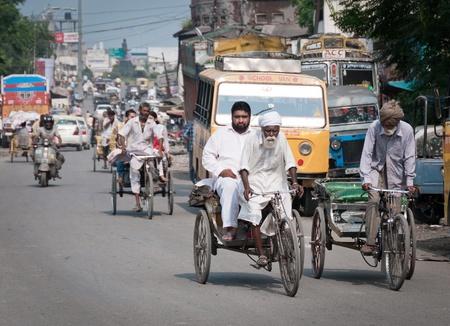 amritsar: Amritsar, India - August 26, 2011 - Old ricksha with passenger, street trafic on background