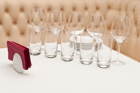 divan: Blanco de mesa con vasos y platos con un div�n de cuero en el fondo. Enfoque en el vidrio frontal.