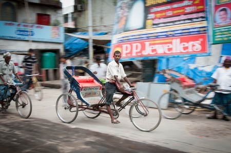 Delhi, India, August 14, 2011- Serious young rickshaw with blurred street on background, shot was made with conducting
