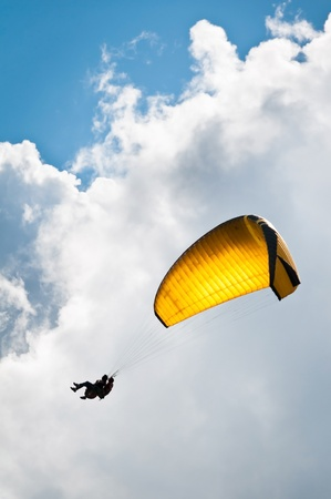Parachuter with instructor descending with a yellow parachute against sky and clouds photo