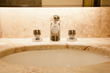 Faucet with two handles and white sink photo
