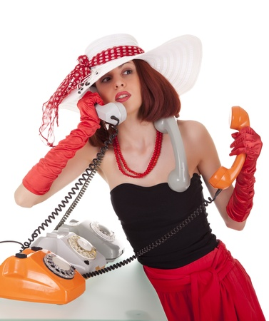 Confused fashion girl in retro style with three vintage phones on white background photo