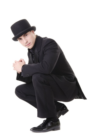 Young attractive man in black suit and hat isolated on white background photo